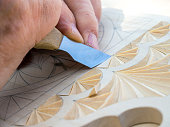 Woodcarver knife creates a geometric pattern on a wooden board.