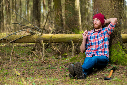 Woodcutter After Work Put Off His Ax And Sat Down Under A Tree To Rest In The Forest Stock Photo - Download Image Now