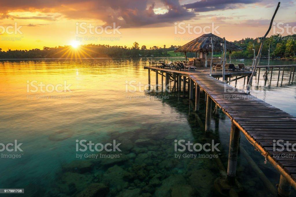 Wooded bridge to Koh Mak harbor at sunset time stock photo