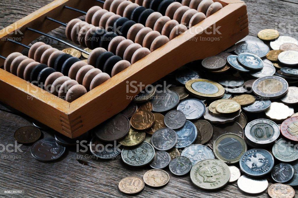 Hölzerne Abacus und eine Reihe von verschiedenen Münzen Lizenzfreies stock-foto