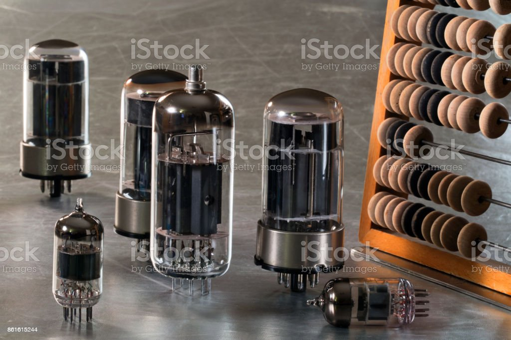 wooden abacus and radio tubes on a metal tray stock photo