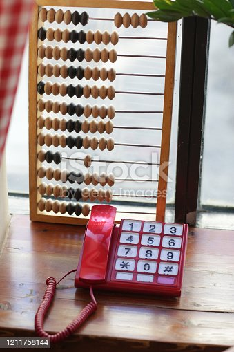 wooden abacus calculating frame and telephone on window background