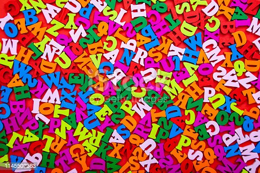 613303142 istock photo Wooden ABC alphabet letters background. Colorful letter on red background. 1145502363