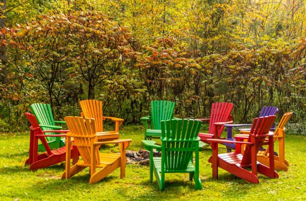 hölzerne adirondack stühle in einem kreis um eine feuerstelle mit herbstfarben angeordnet. - kanada rundreise stock-fotos und bilder