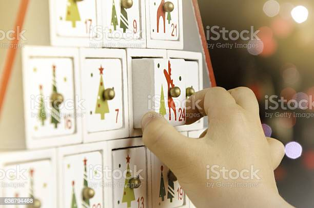 Child's hand pulling the last drawer (number 24) of a wooden advent calendar Christmas tree.