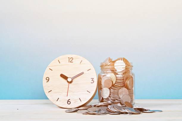 reloj despertador madera y monedas en fondo blanco - trabajar hasta tarde fotografías e imágenes de stock