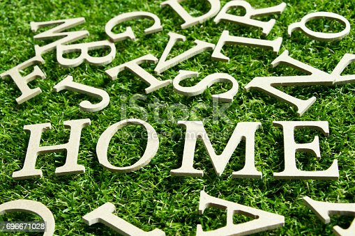 1081572480 istock photo Wooden alphabet in wording home on artificial green grass background 696671028