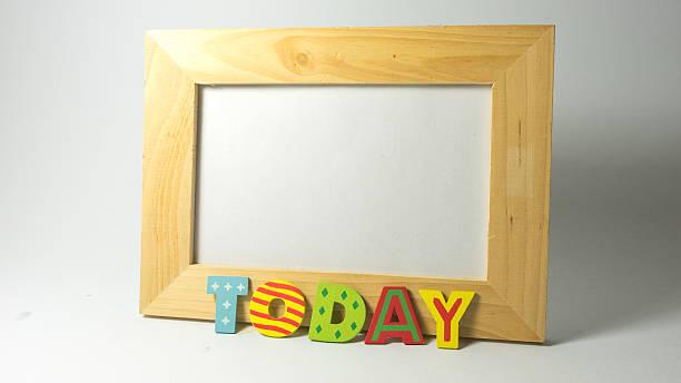 hölzerne alphabet buchstaben bilden wort auf täglich leere foto frame - wetter dienstag stock-fotos und bilder