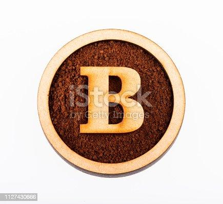 istock B, wooden alphabet letter - Ground organic coffee. Coffea 1127430666