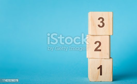 Wooden alphabet number blocks 123 on blue background, copy space