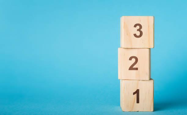 blocos de madeira do número do alfabeto 123 no fundo azul - dois objetos - fotografias e filmes do acervo