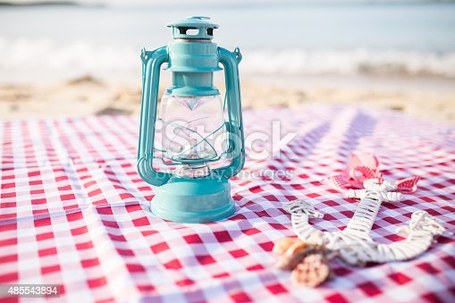 istock Wooden anchor, seashell and lantern on a sandy beach. 485543894
