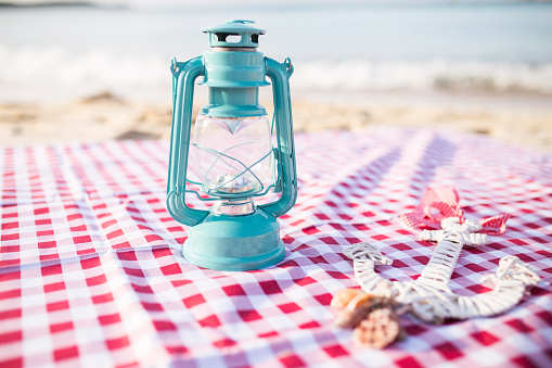 istock Wooden anchor, seashell and lantern on a sandy beach. 485543894
