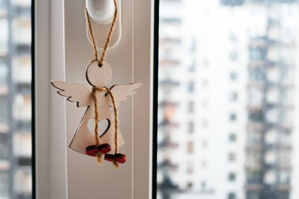 Un ange en bois avec un trou en forme de coeur accrochant sur un cordon ciré sur une poignée de fenêtre sur un fond brouillé des maisons voisines. Charme protecteur avec des coeurs rouges sur une dentelle autour du cou - Photo