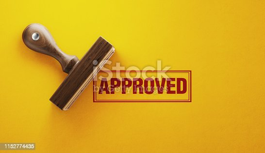 Wooden approved stamp on yellow background. Horizontal composition with copy space.