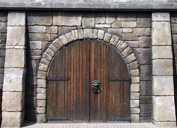 wooden arched doors surrounded by stones in medieval design - castle stock photos and pictures