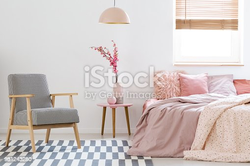 istock Wooden armchair on patterned carpet in pink bedroom interior with flowers next to bed. Real photo 981243280