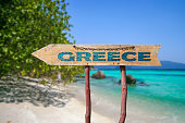 Wooden arrow road sign with word Greece against beach background. Travel to Greece concept.