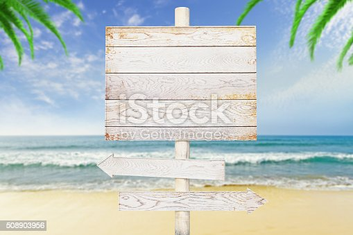 istock Wooden arrow signs on beach background 508903956