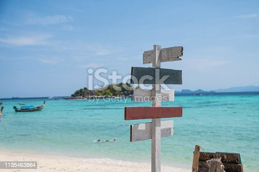 istock Wooden arrows signpost on white beach with tropical sea 1135463864