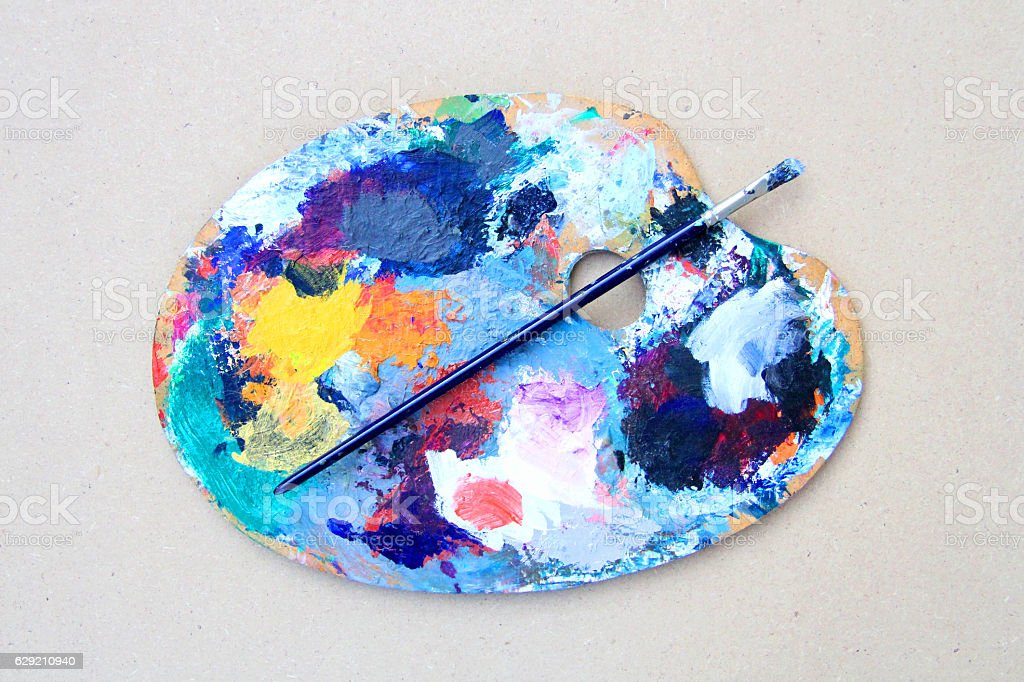Wooden art palette with colourful paints and brush stock photo