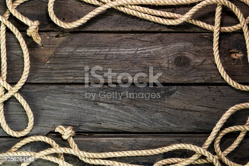 istock Wooden background from an old board with hemp rope 1256264142