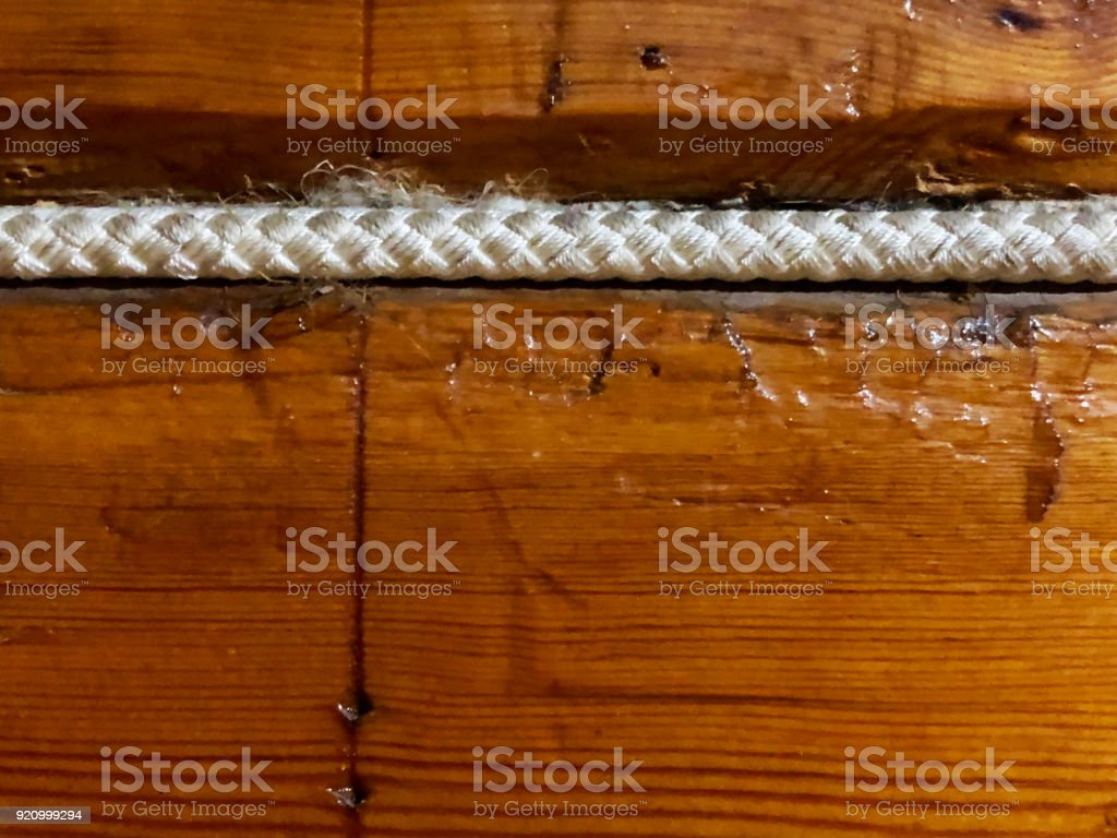 Wooden background of boards with a rope in the seam stock photo