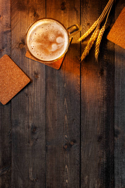 Wooden background with beer mug and wheat ears in the rays of the sunset stock photo