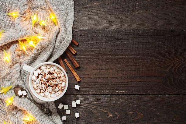wooden background with cup of cacao, marshmallow and garland - wärmeplatte stock-fotos und bilder