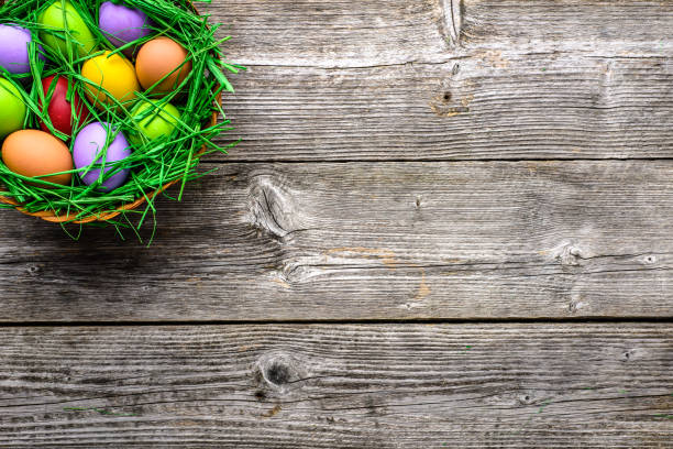 Wooden background with easter eggs in the basket, top view stock photo