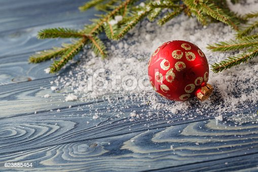 Wooden background with fir branch and christmas bauble. Copy-space.
