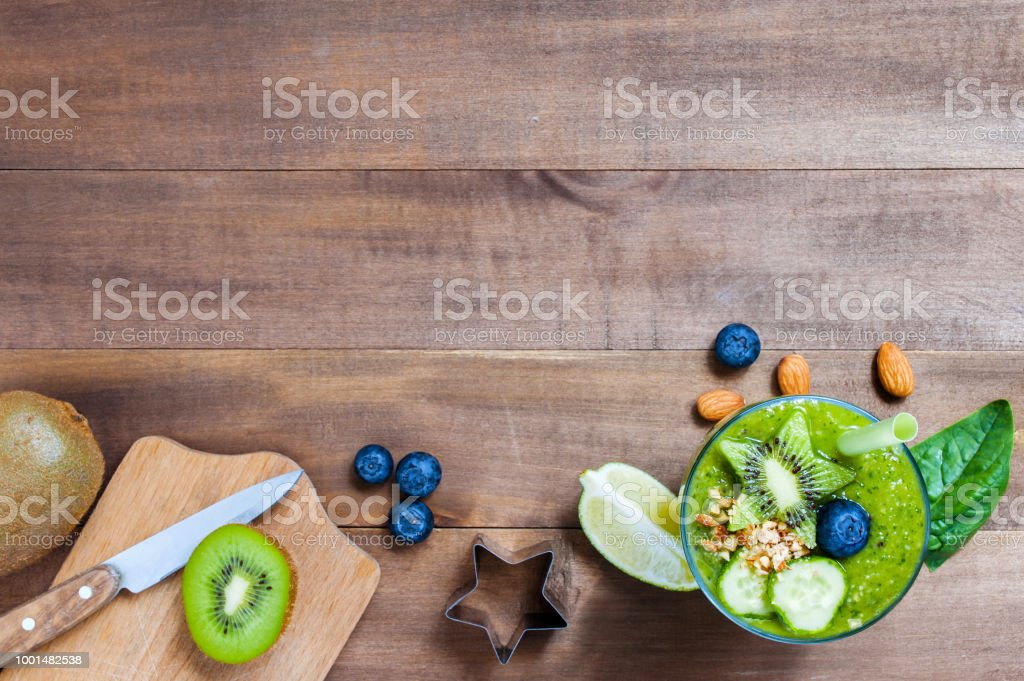 Wooden background with glass of green healthy smoothie stock photo