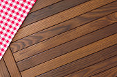 Wooden background with red and white checkered tablecloth