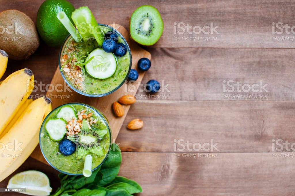 Wooden background with two glasses of green healthy smoothie stock photo