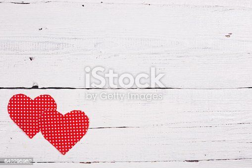 istock Wooden background with two red hearts 642295982
