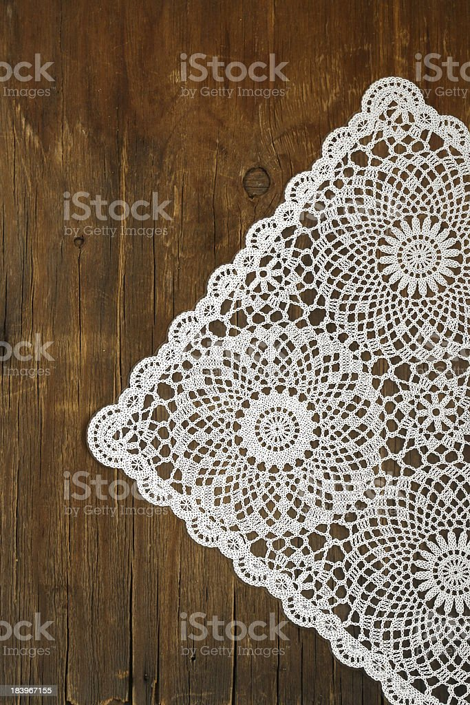 wooden background with white lace vintage napkin stock photo