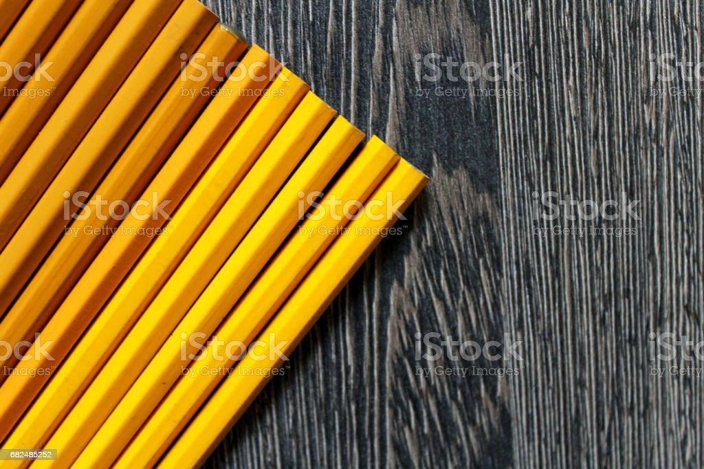 Wooden background with yellow and orange pencils. Lizenzfreies stock-foto
