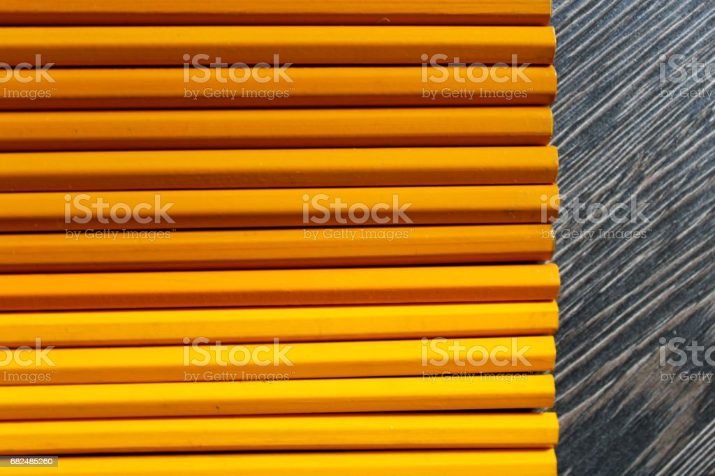 Wooden background with yellow and orange pencils. Lizenzfreies stock-foto