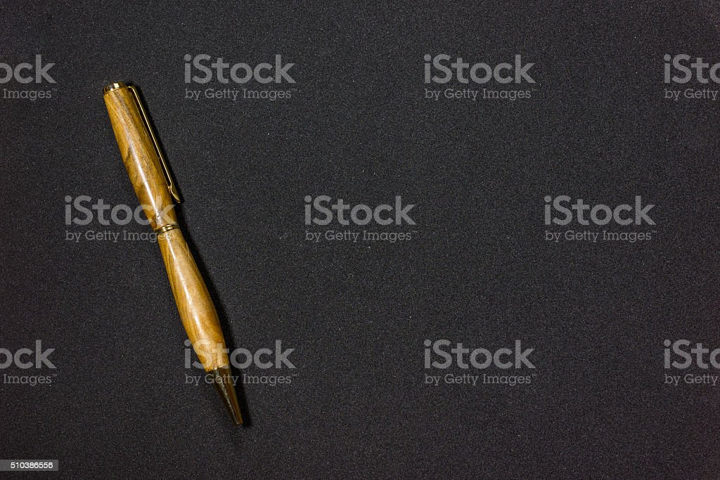Wooden ballpen on black stock photo