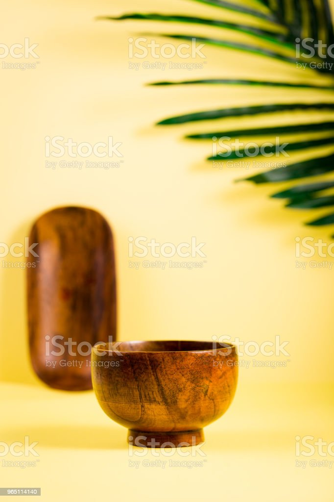 Wooden bamboo Asian food spa bowls on yellow tropic summer background royalty-free stock photo