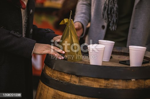 Tilt shot of a wooden barrel with golden gift box and disposable white cups on top of a where a male hand is taking one cup and female hands the gift.