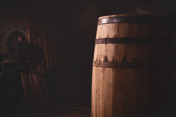 wooden barrel on a dark background, in a workshop, in an old room. - barrica imagens e fotografias de stock