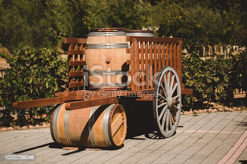 Wooden barrel with red and wihte wine for tasting in cart on the vineyard. Textured object.