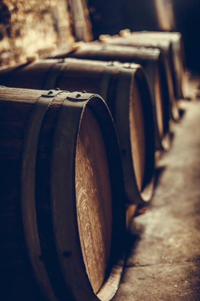 Wooden barrels in a dark cellar stock photo