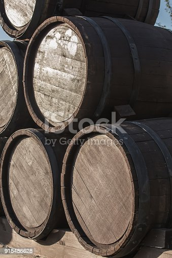 Wooden barrels in a pile on a pallet. Closeup.