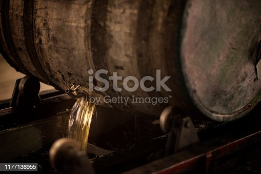 Old wooden barrel pouring rum in a distillery.