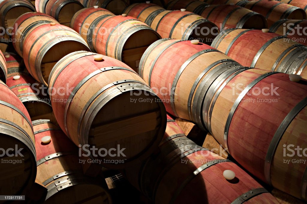 Wooden barrels stacked atop one another in a dimly lit area royalty-free stock photo