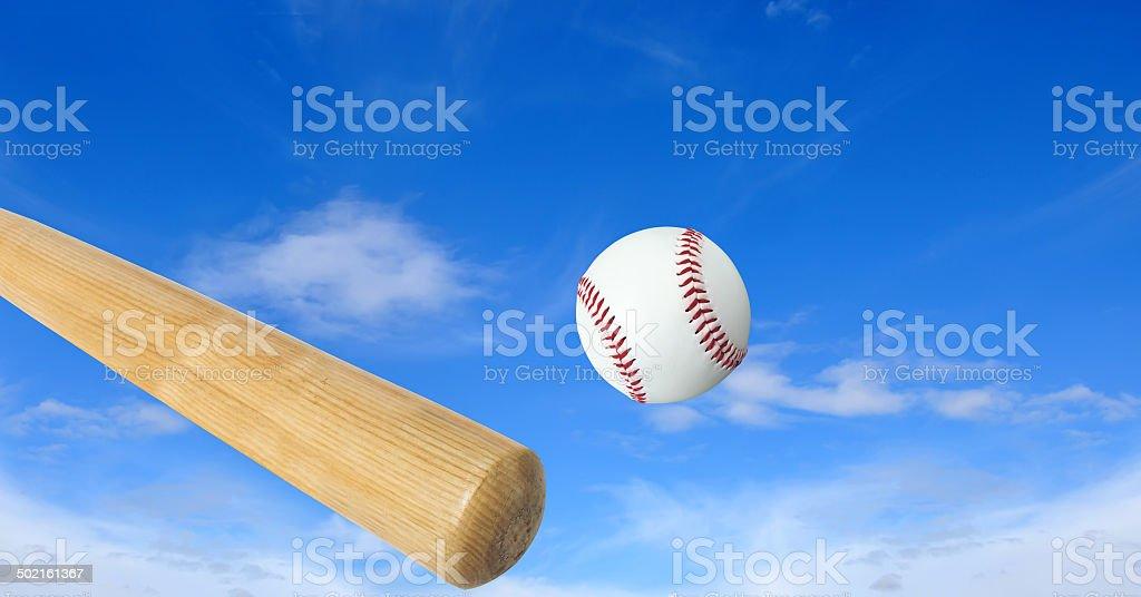 Wooden baseball bat and ball over blue sky