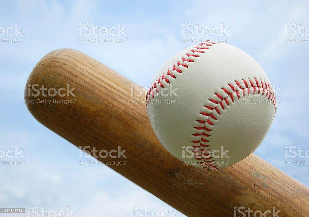 Wooden bat hitting a baseball with red stitching stock photo
