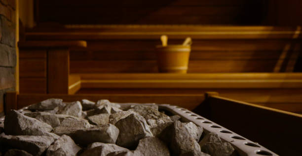 Wooden Bathhouse with a heating pot filled with stones, close up. Wooden sauna interior with equipment, coals, ladle, bucket. Wooden Bathhouse with a heating pot filled with stones, close up. Wooden sauna interior with equipment, coals, ladle, bucket. sauna stock pictures, royalty-free photos & images